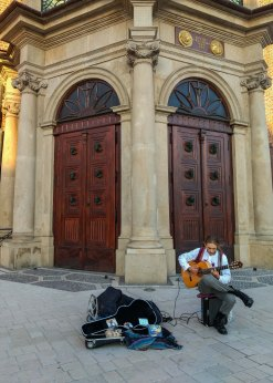 Street artist singing and playing in krakow, poland