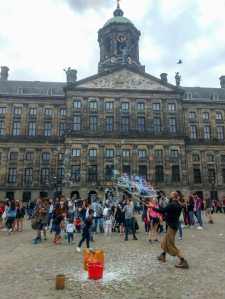 A guy making big air bubbles and playing with kids in front of museum